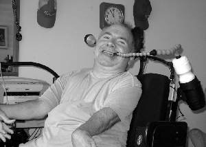 Photo of Bob Maloney smiling and using his Drink Aid.