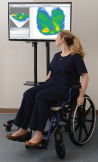 Woman in wheelchair observing digital pressure mapping image on a screen.