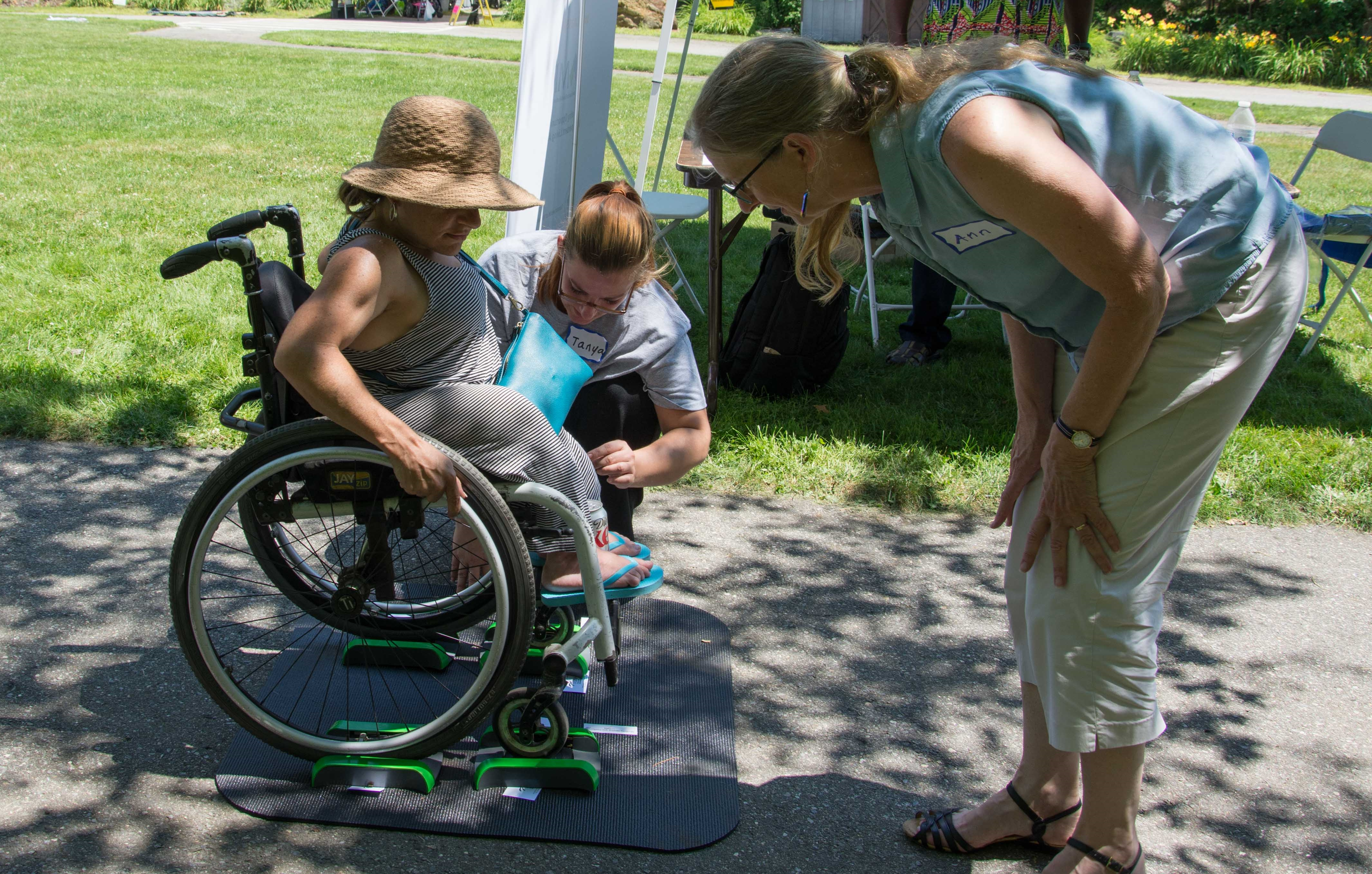 A woman in a wheelchair tries out a portable scale with the assistance of two women