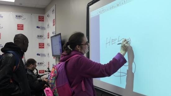 A teenage girl draws on the smartboard using a stylus.