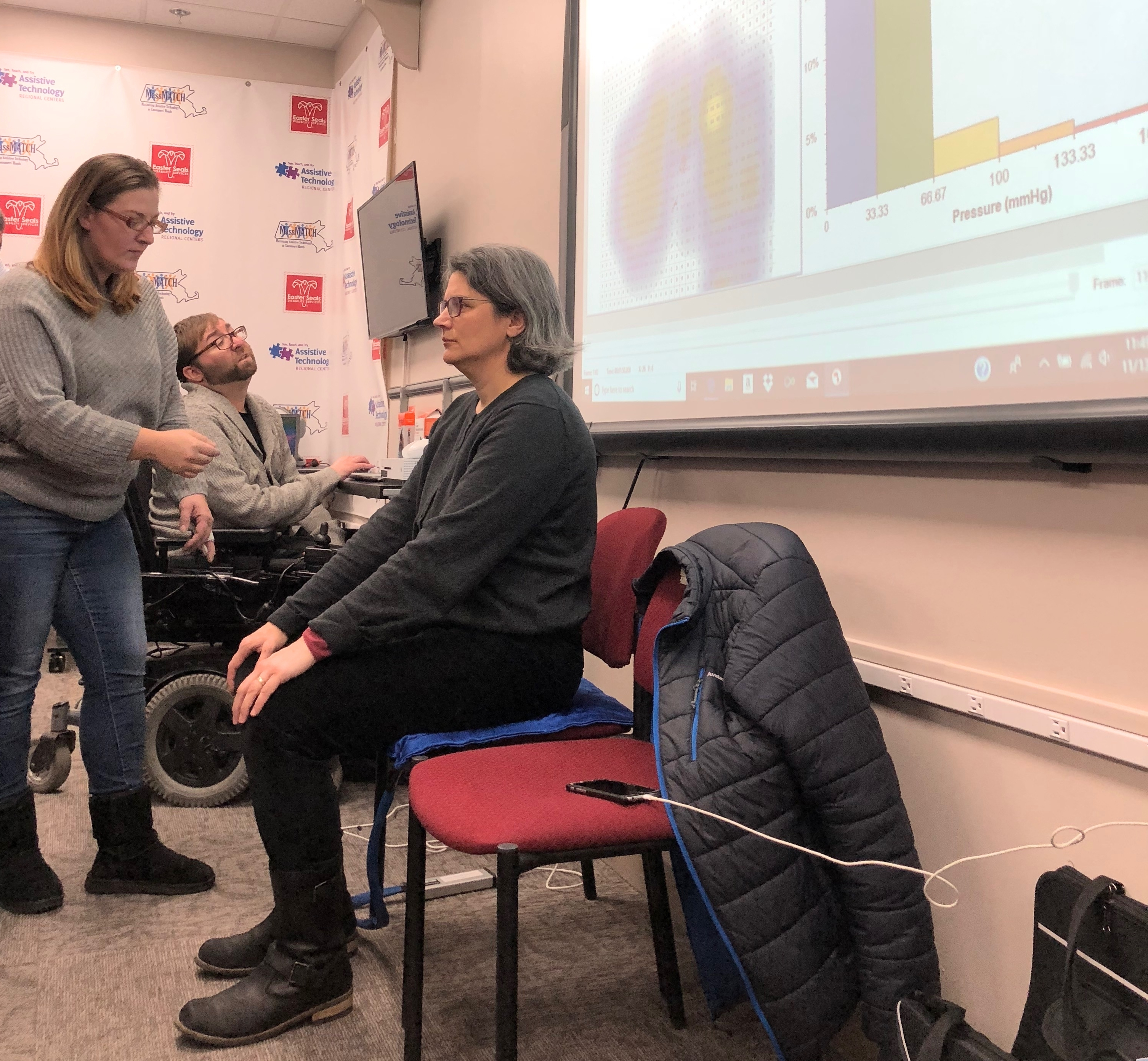 A woman seated on a pressure mapping system with a Smart Board displaying graphs. A man in a wheelchair in the background and another woman standing, helping operate the equipment.