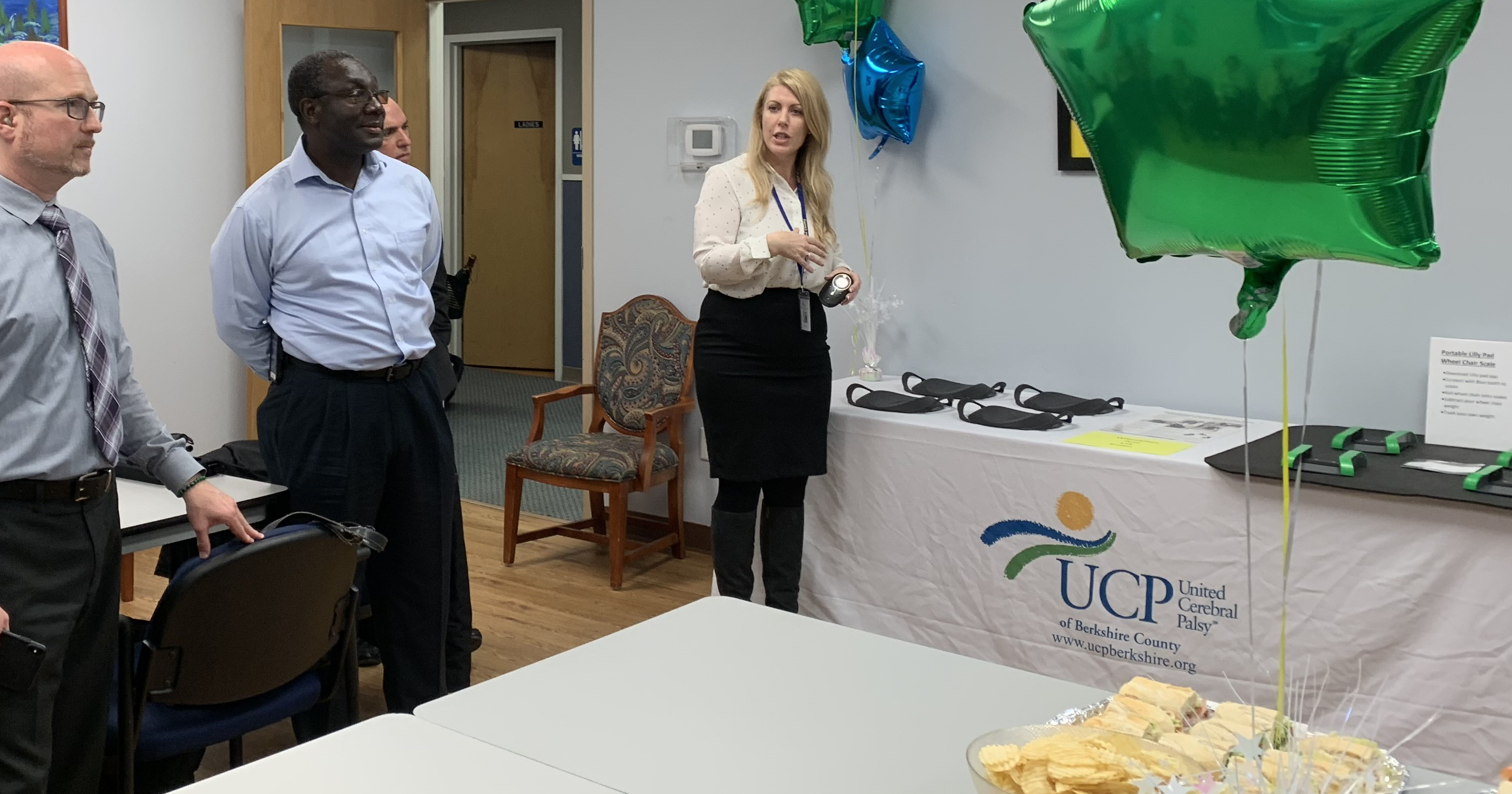 A woman speaking holding a device next to a table with equipment and an UCP banner. There are balloons and food on a table in the foreground. Three men stand listening.