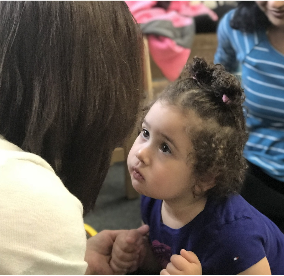 A little girl gazes into the eyes of a teacher who holds her hands