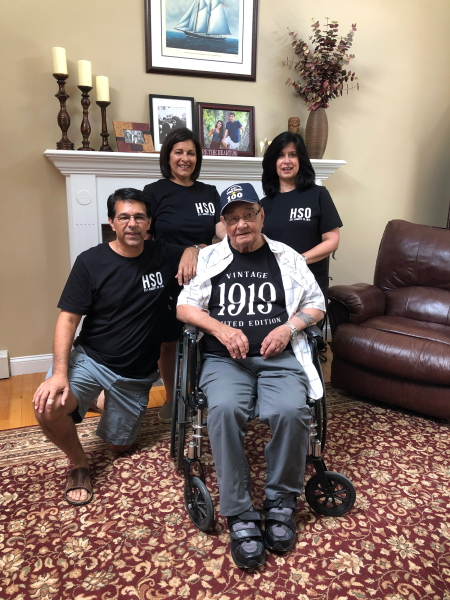 A man seated in a wheelchair surrounded by a kneeling man and two women behind. They are in a livingroom.