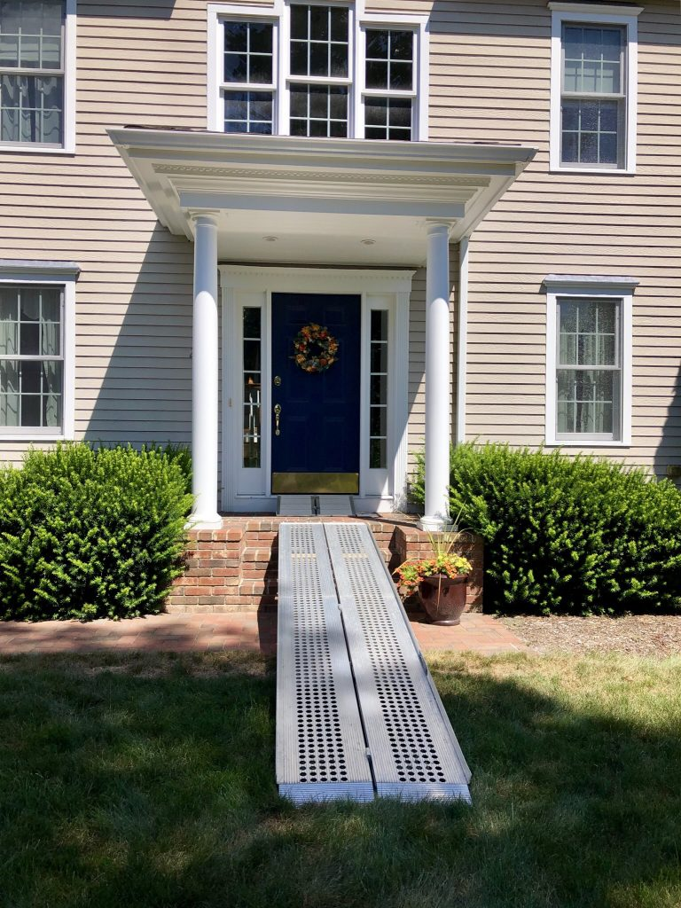 A house with portable ramps leading from the lawn to the front doorway.