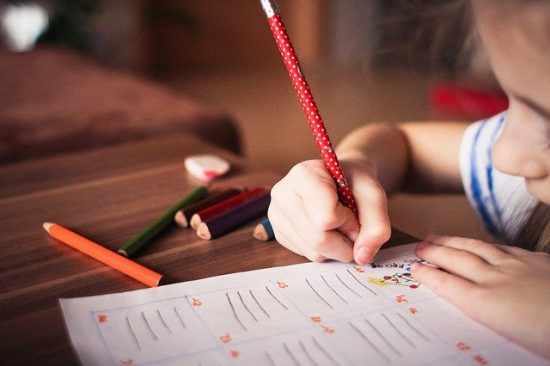 A child works on a worksheet with colored pencils.