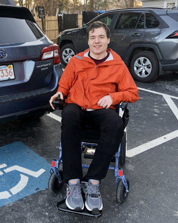 A man seated in a wheelchair smiling in a parking lot with accessible parking icon painted on pavement.